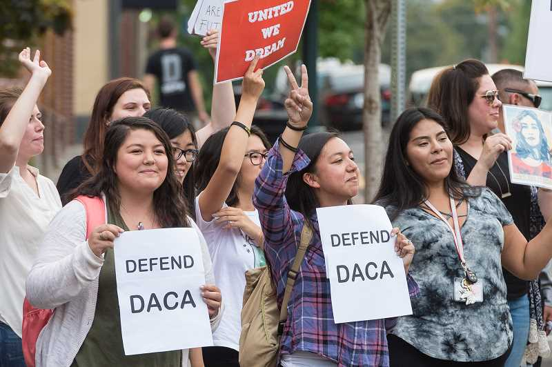 NEWS-TIMES PHOTO: CHRISTOPHER OERTELL - DACA supporters respond to supportive honks from passing cars.