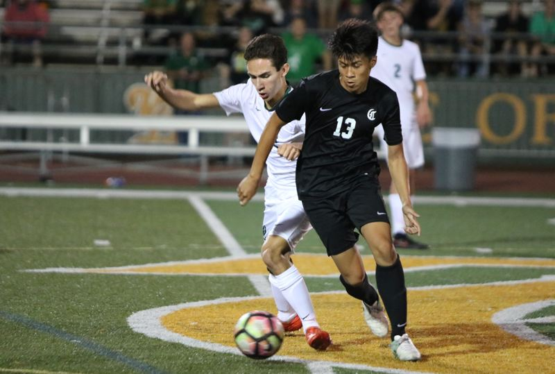 REVIEW/NEWS PHOTO: JIM BESEDA - Clackamas' Tyler Nguyen (13) maneuvers around West Linn's Marco Kreske during the second half of Thursday's non-conference boys' soccer game at West Linn High School.