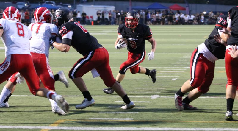 REVIEW/NEWS PHOTO: JIM BESEDA - Clackamas' James Millspaugh (9) scored on a 2-yard run to give the Cavaliers a 21-0 lead in the second quarter of Friday's non-conference home game against Lincoln.