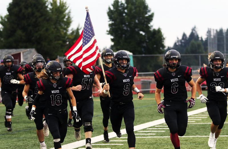 DAN BROOD - Tualatin junior Kyle Dernedde (with flag) leads the Wolves onto the field prior to Friday's game against Battle Ground.