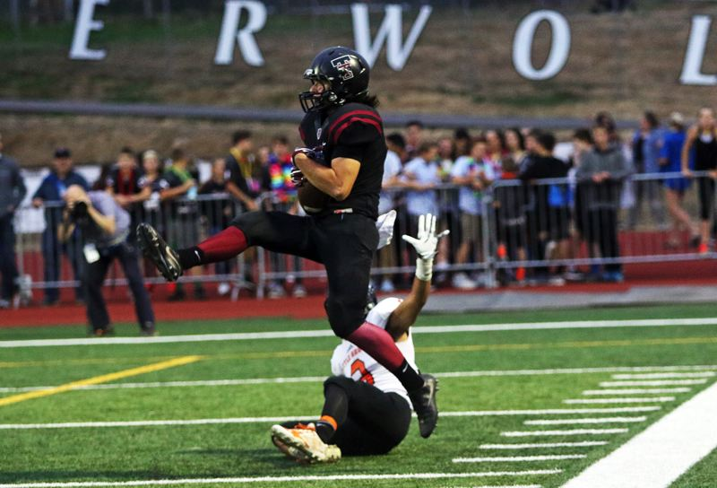 DAN BROOD - Tualatin senior receiver Jackson Willig makes a leaping catch for a 31-yard gain in the first quarter of Friday's game.