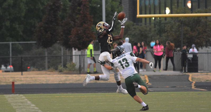 TIMES PHOTO: MATT SINGLEDECKER - Southridge junior wide receiver Keyvaun Eady goes up high for a catch against Tigard.