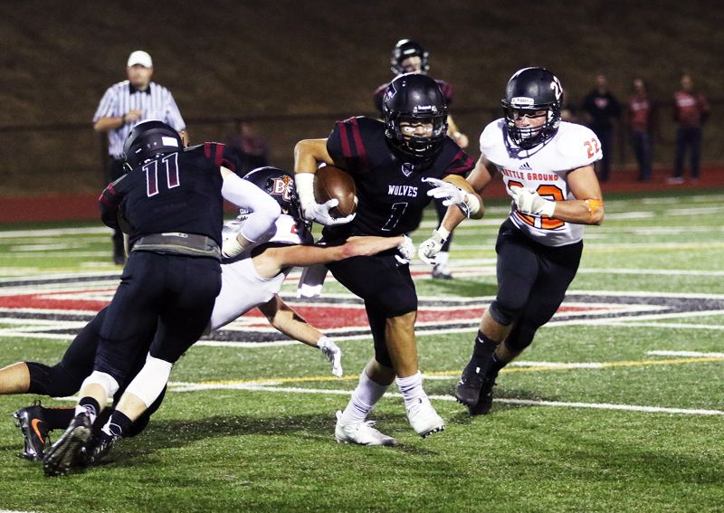 DAN BROOD - Tualatin junior receiver Jett Searle (1) looks for running room.