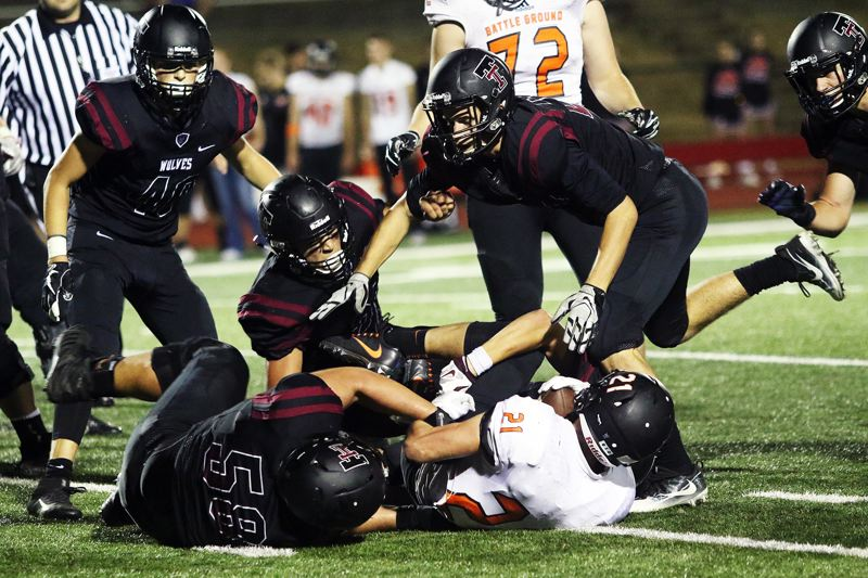 DAN BROOD - The Tualatin defense swarms to bring down Battle Ground running back Brock Robinson.