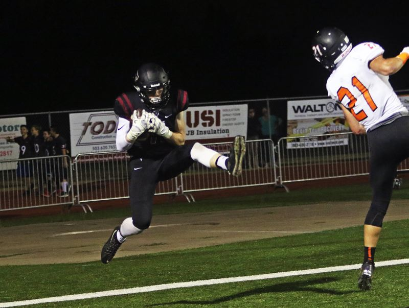 DAN BROOD - Tualatin senior receiver Nick Savage makes a jumping catch in the end zone for a touchdown.