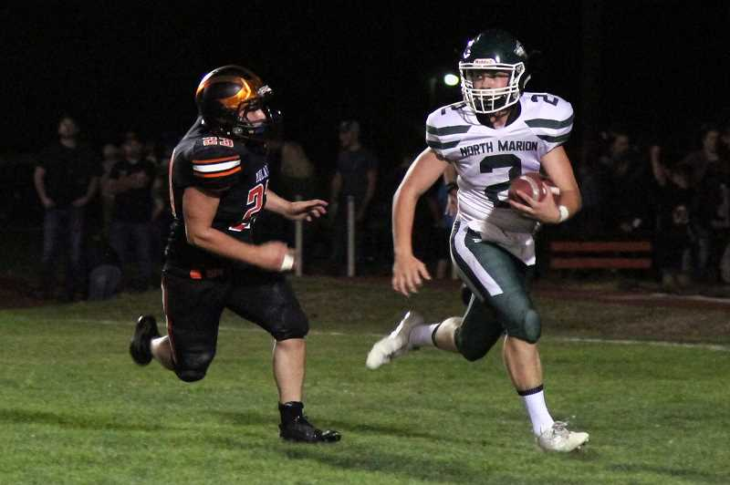 PHIL HAWKINS - Molalla junior Grant Riehle chases down North Marion sophomore Dylan Dedolph in the end zone for a safety in a defensive battle between the Indians and the Huskies on Friday night.
