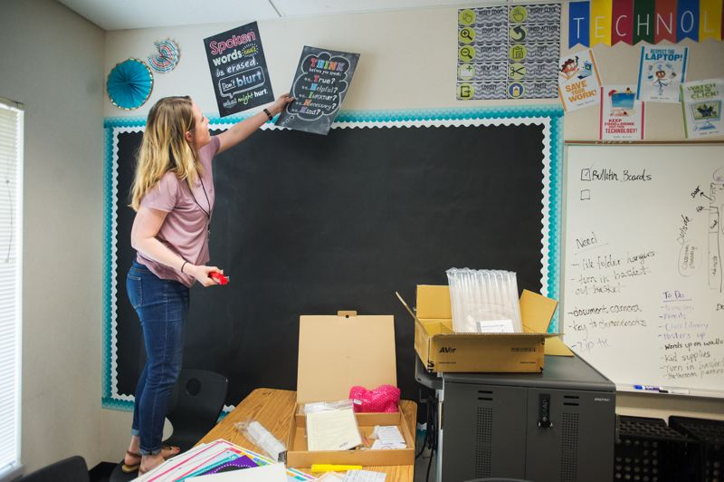 OUTLOOK PHOTO: JOSH KULLA - Amanda Ewing puts up posters to encourage kindness and cooperative behavior in her new Kelly Creek Elementary School classroom.