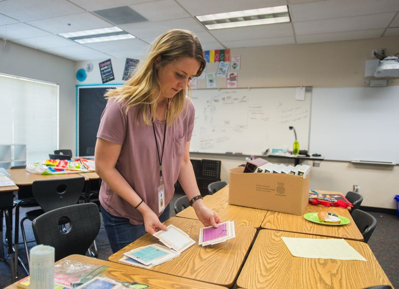 OUTLOOK PHOTO: JOSH KULLA - Ewing sorts some materials she plans to use with her new fifth grade students. The former social worker said a teaching stint in a rough section of Miami made her realize she needed more experience.