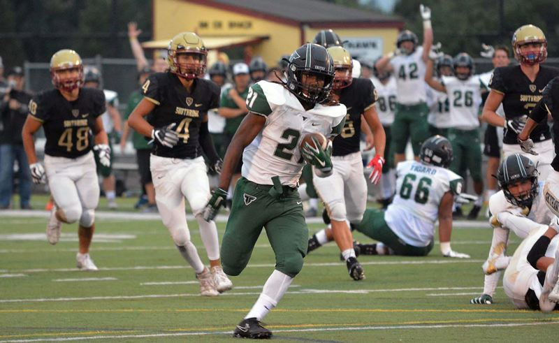 TIMES PHOTO: MATT SINGLEDECKER - Tigard's Malcolm Stockdale races away from the Southridge defense during his team's 48-12 win over the Syhawks at Southridge High School on Friday night.