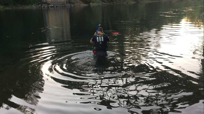 CONTRIBUTED PHOTO - A Clackamas Fire rescue swimmer dives into the water to confirm that a submerged vehicle at Barton Park was unoccupied.