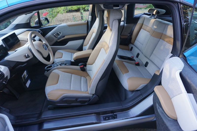 PORTLAND TRIBUNE: JEFF ZURSCHMEIDE - Inside, the i3 reminds you that you chose the futuristic option. From the reverse-opening rear doors to the living-room arrangement of the wood, plastic, and cloth dashboard and trim, the i3 is again unlike other cars.