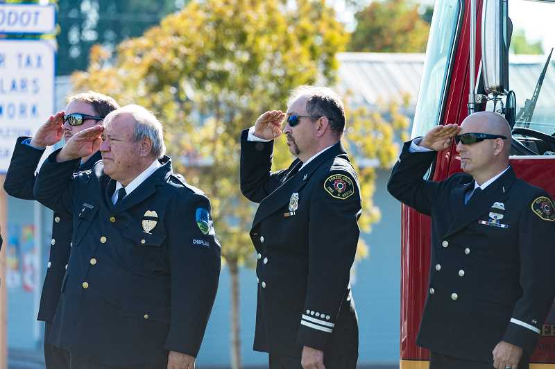 NEWS-TIMES PHOTO: CHRISTOPHER OERTELL - First responders salute as the flag is lowered to half mast.  A firefighter also rang a fire bell 15 times — three sets of five times each, the old firefighter down signal, as onlookers watched silently.