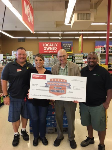 PHOTO COURTESY: MICHAEL CLARK - Pioneer Pantry coordinators Ted Thonstad and Jesse Cry (right) accept a check from Grocery Outlet owners/operators Sarah and Dan Mills.