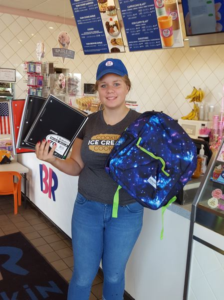PHOTO COURTESY: LESLIE ROBINETTE - Baskin-Robbins employee Kennedy Roby shows off some of the school supplies donated by customers.