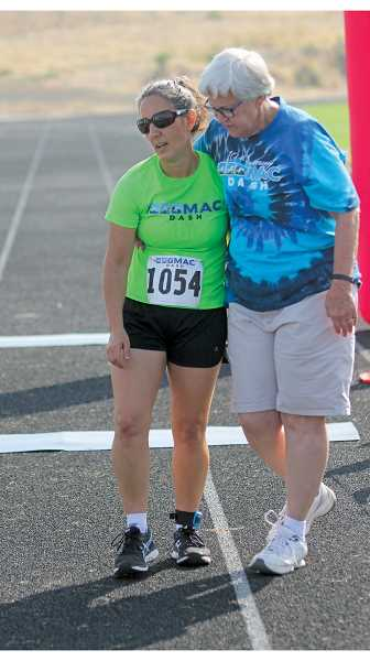 """WILL DENNER/MADRAS PIONEER - Former MAC Dash race director Suzy El-Attar (left), who competed in the coed division on the team, """"Doug, Dave and the Diva"""" is greeted by Margee O'Brien at the finish line."""
