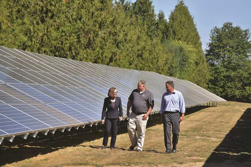 SUBMITTED PHOTO: GREG LEO - (Pictured from right) Shaun and Larry George, owners of Northwest Hazelnut, tour the thousand-panel solar array with Gov. Kate Brown at the Northwest Hazelnut processing plant in Hubbard.