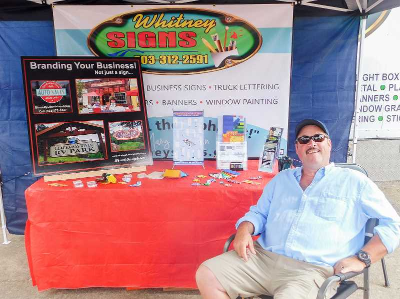 ESTACADA NEWS PHOTO: EMILY LINDSTRAND - Estacada Mayor Sean Drinkwine represented Whitney Signs at the community trade fair last weekend. He thought that the events bustling atmosphere indicated that the local economy was doing well.