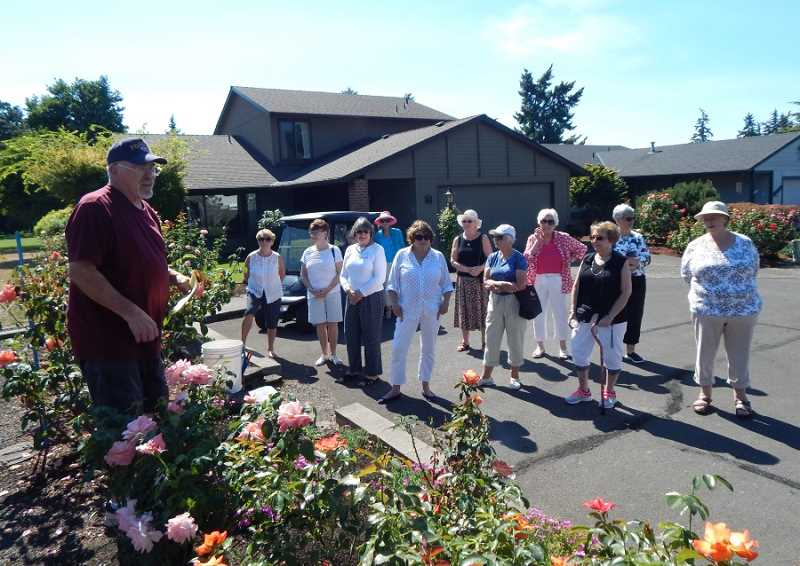BARBARA SHERMAN - Larry McCullough stands in the Summerfield rose garden at the end of Highland Drive and tells members of the Summerfield Garden Club about the garden's history and how he maintains the plants.