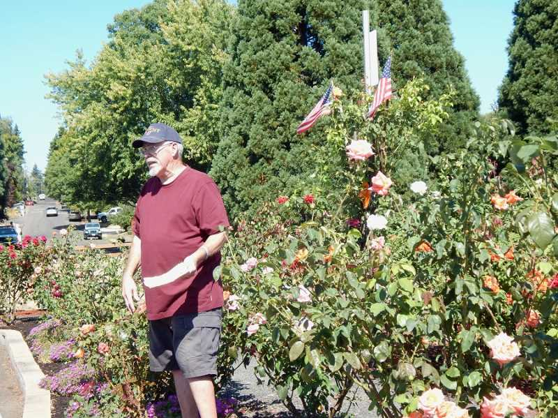BARBARA SHERMAN - Larry McCullough, a retired firefighter, has created a patriotic centerpiece in the Summerfield rose garden; to the left is 100th Avenue, which according to city of Tigard long-range plans may someday connect to Highland Drive.