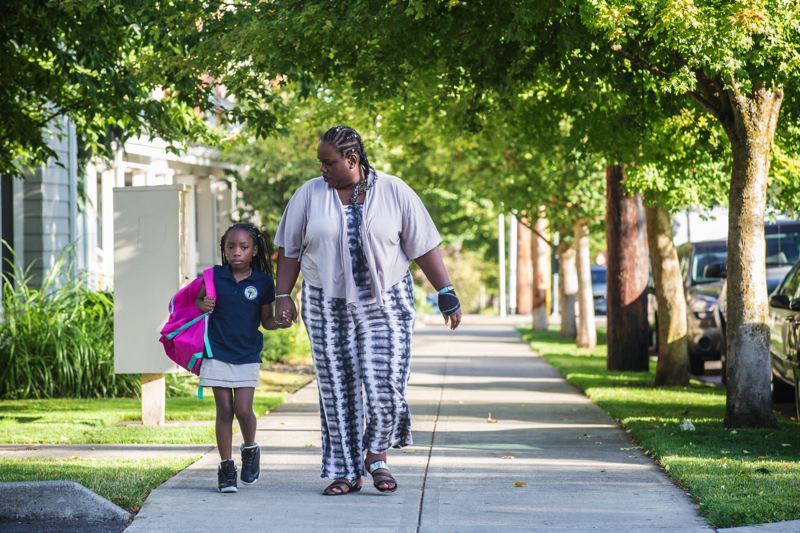 THE PORTLAND TRIBUNE/JONATHAN HOUSE - Lydia Gray-Holifield walks her daughter, Georgy'e, to KairosPDX charter school in North Portland. A proposal to redraw school boundaries and move programs in North and Northeast Portland would push the majority-black charter school out of the old Humboldt Elementary School. ACCESS Academy, which was 70 percent white last year, would move in.