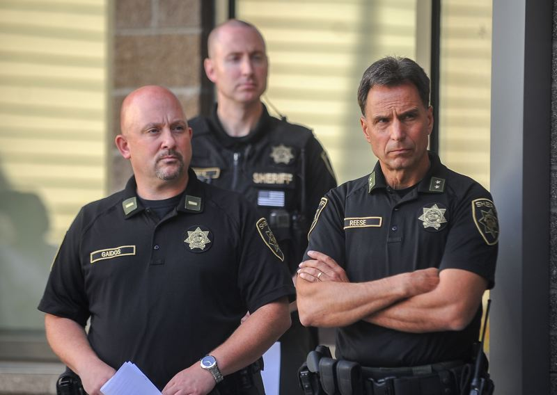 OUTLOOK PHOTO: JOSH KULLA - Lt. Chad Gaidos and Sheriff Michael Reese listen during a press conference in Troutdale on Wednesday, Sept. 13. Sgt. Bryan White stands behind them.