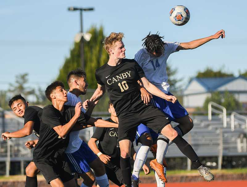 OUTLOOK PHOTO: JOSH KULLA - Gresham's Joel Gonzalez and Canby's Joe Thompson fight for a header off a corner kick Tuesday as the Gophers dropped the Cougars 4-1 in a non-league boys prep soccer matchup at Gresham High School.