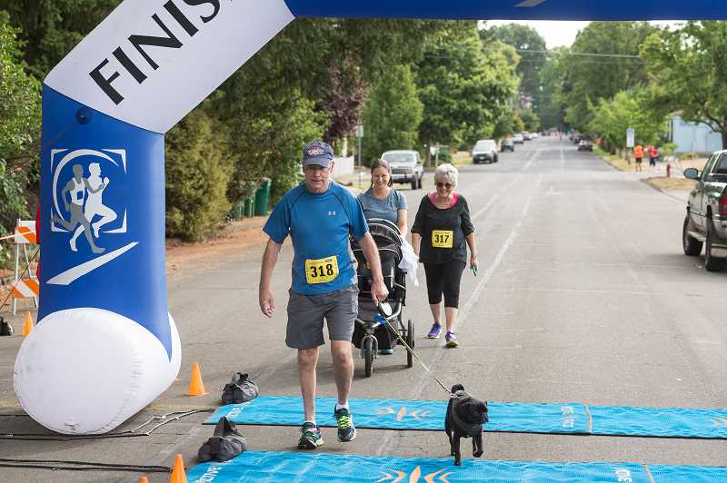 NEWS-TIMES PHOTO: CHRISTOPHER OERTELL - Ron Cole and his dog cross the finish line together.