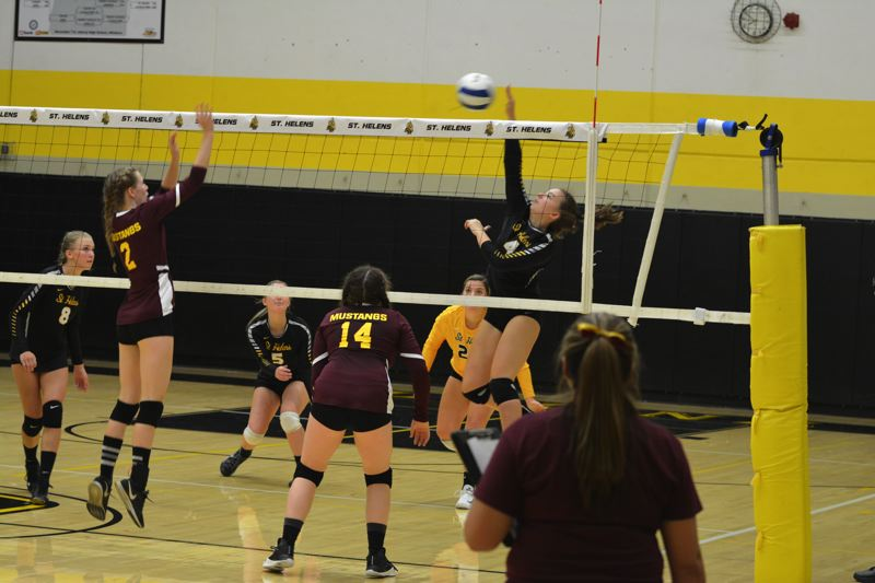 SPOTLIGHT PHOTO: JAKE MCNEAL - Lions junior outside hitter Natalee Webster (4) shoots over Milwaukie senior middle blocker Justine Brown (2) and sophomore setter Maria-Lucia O'Doherty (14).