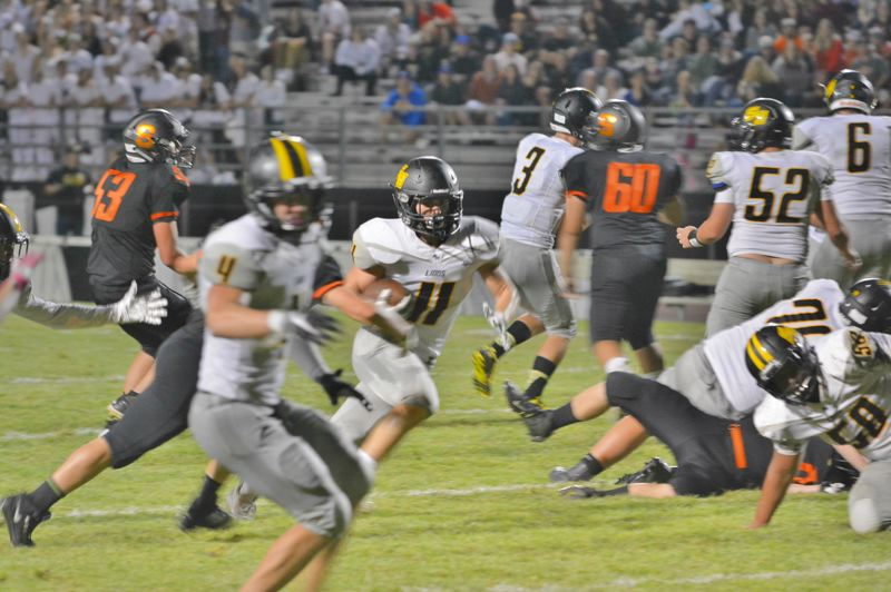 SPOTLIGHT PHOTO: JAKE MCNEAL - Lions junior running back Cade Duarte (11) runs through a hole in the middle of the field.