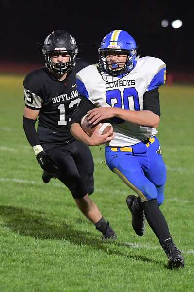 LON AUSTIN/CENTRAL OREGONIAN - Kyle Knudtson carries the ball around left end for a big gain in the second half of the Cowboys loss to the Sisters Outlwas Friday night. Knudtson led the Cowboys in rushing with 71 yards and one touchdown.