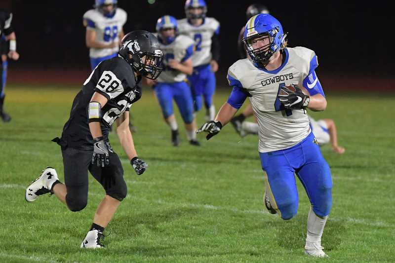 LON AUSTIN/CENTRAL OREGONIAN - Jacob Kasberger sprints around Jared Richerson of Sisters for a first down.