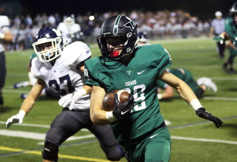 DAN BROOD - Tigard senior running back Spencer Smith gets to the outside.