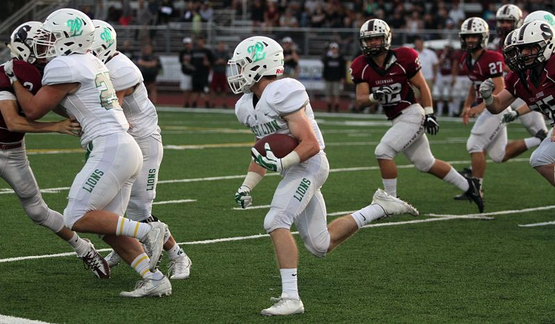TIDINGS PHOTO: MILES VANCE - West Linn's James Marshall takes the opening kickoff against Sherwood back for 93 yards and a touchdown in the Lions' 42-21 victory at West Linn High School on Friday.