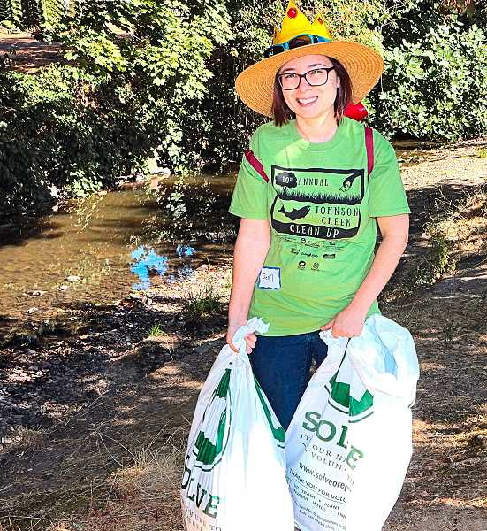 DAVID F. ASHTON - JCWC volunteer Jenn Arra hauls a bag of trash up out of Johnson Creek.