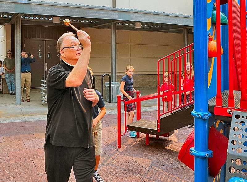 DAVID F. ASHTON - St. Agatha Catholic Church's Father Nathan Zodrow blesses the play structure, with a sprinkling of holy water.