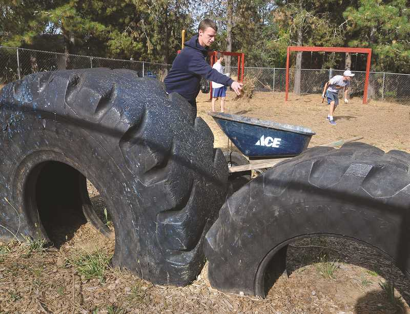GARY ALLEN - George Fox University students and staff congregated at North Valley Friends Church to, among other things, weed and level the children's playground.