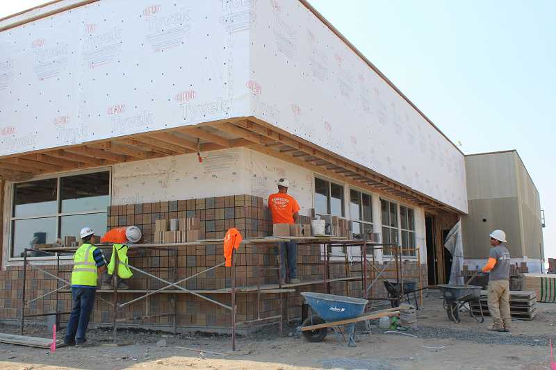 HOLLY M. GILL - A crew installs decorative concrete block on the north and east walls of the Plateau Travel Center, located on Cherry Lane, in the Madras Industrial Site.