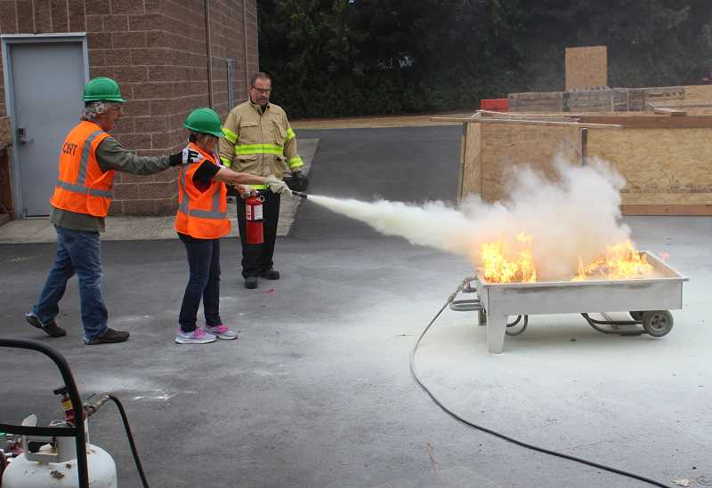 REVIEW PHOTO: ANTHONY MACUK - Lake Oswego CERT graduates Al Fagundes (left) and Sue Squires practice using a fire extinguisher under the guidance of LO Fire Marshal Gert Zoutendijk.