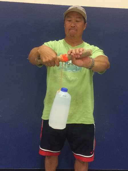 COURTESY PHOTO - NAMS PE teacher Darren Pang demonstrates the use of the schools old fitness equipment, old milk jugs on strings.