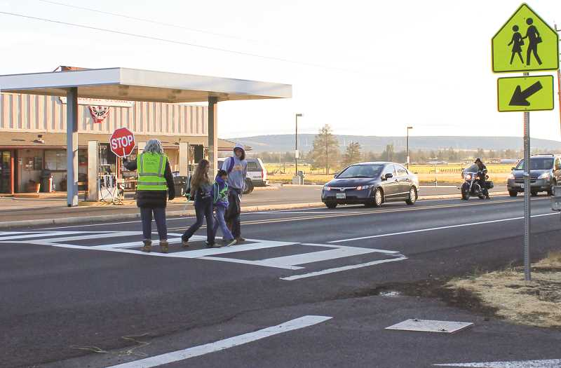 HOLLY SCHOLZ - Powell Butte Community Charter School educational assistant Barbara Burns helps students cross Highway 126 in front of the school. Burns said she stops traffic 10 or 12 times each morning between 7:15 and 7:45 a.m. to allow students to cross from the Powell Butte Country Store to the school. Each afternoon from 2:30 to 2:40, a crossing guard helps children cross the street.