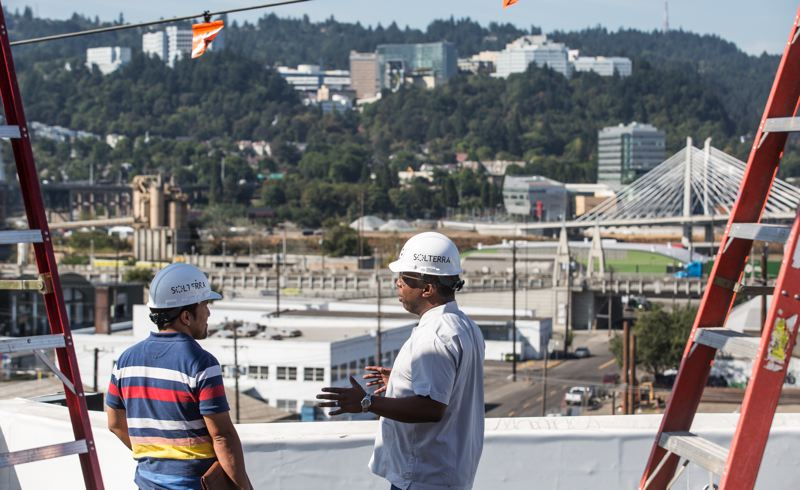 PAMPLIN MEDIA GROUP: JONATHAN HOUSE - Workers on the roof of the new SolTerra headquarters building at 9th and S.E. Division Street. That white edge will eventually be an infinity edge of greenery.