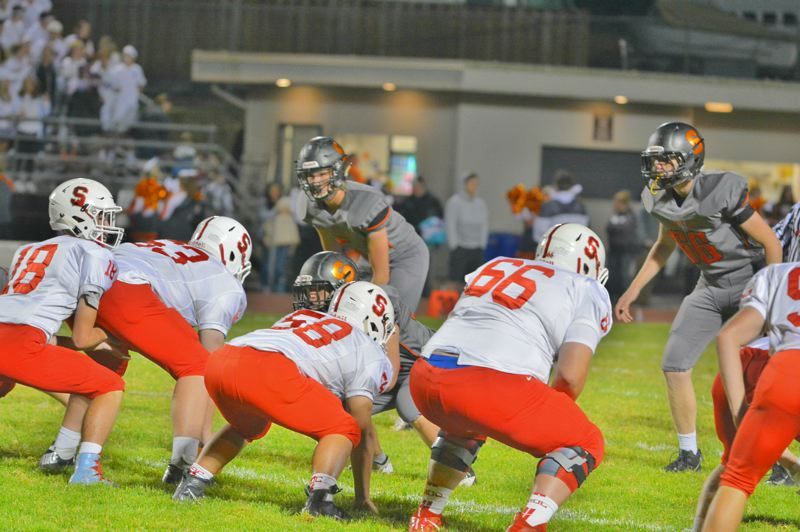 SPOTLIGHT PHOTO: JAKE MCNEAL - Scappoose senior linebacker Willy Lohman (5) and sophomore defensive lineman Slater Smiens (66) anticipate a snap from Seaside sophomore quarterback Ledger Pugh (18).