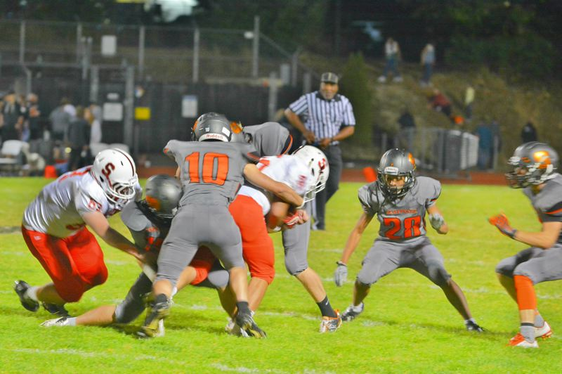 SPOTLIGHT PHOTO: JAKE MCNEAL - Scappoose sophomore Connor Maclachlan (10) and sophomore safety Kawika Napaa (28) meet for a tackle.