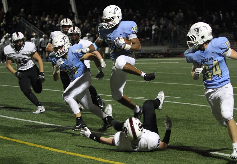 REVIEW PHOTO: MILES VANCE - Lakeridge sophomore running back Jalen John hurdles a defender during his team's 49-42 overtime win over Sherwood at Lakeridge High School on Friday.