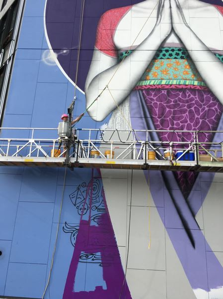 PAMPLIN MEDIA GROUP: JONATHAN HOUSE - The Osolterra mural in progress. Instead of a grid, artist Fin DAC used hand drawn faces, visible in black below his platform.