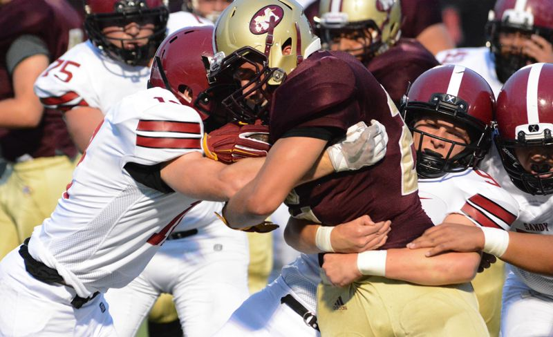 SANDY POST:DAVID BALL - Sandy's Colby Carson (9) wraps his arms around the waist of Milwaukie running back Chazz Amundson during the first half of Friday's Northwest Oregon Conference game at Milwaukie.