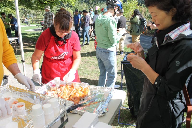 TRIBUNE PHOTO: LYNDSEY HEWITT - Salmon is served up straight from the fire at Westmoreland Park on Sunday.