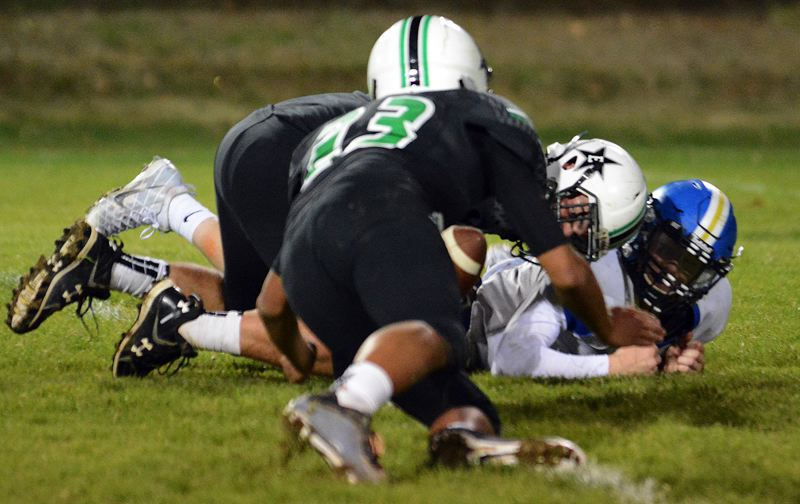 NEWS PHOTO: DAVID BALL - Estacada linebacker Gabriel Martinez dives on the loose ball after teammate Hunter Gotchall forced a fumble in the fourth quarter.