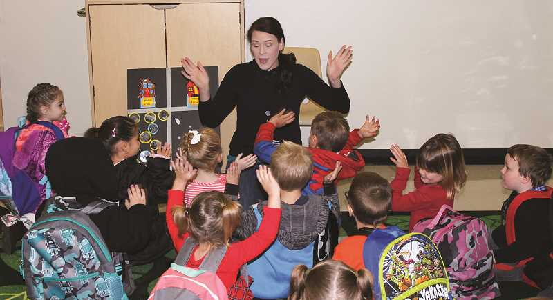 "HOLLY SCHOLZ - Head Start assistant teacher Jenna Smith leads her students in the ""Hello"" song first thing Monday morning at the new Head Start classroom at Ochoco School Crossing. Although the preschoolers attended class part-time last week, Monday was the first full week of full-day Head Start in Prineville."
