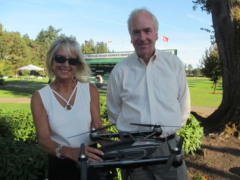 PHOTO BY DICK TRTEK - Lori Brown and David Jacobsen are pictured in front of the scoreboard prior to the conclusion of the U.S. Senior Women's Amateur Championships held at Waverley Country Club in Milwaukie.